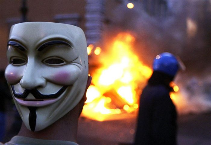 a_protester_wearing_a_guy_fawkes_mask_look_on_as_a_4e99ecf946