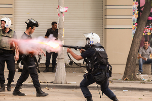 A police officer fires teargas on June 17, 2013. © 2013 Miguel Carminati