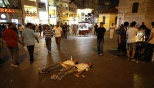 Two protesters lie on the ground of Taksim Square as they stage a silent protest in Istanbul