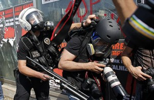 A Turkish riot policeman pushes a photographer during a protest at Taksim Square in Istanbul
