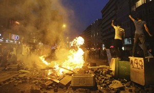 Anti-government protesters shout slogans as they stand on barricades in Istanbul