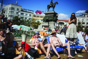 "Protesters sunbathe during an initiative called ""Beach revolution"" as part of demonstration in front of parliament in Sofia"
