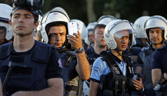 A riot policeman uses a mobile phone to film protesters at Taksim Square in Istanbul