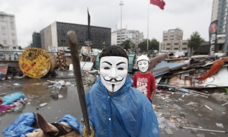 A boy wearing a Guy Fawkes mask in Gezi Park