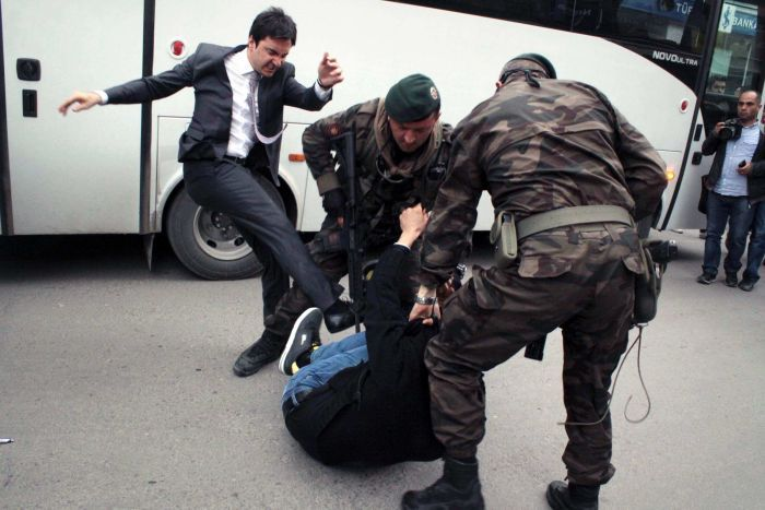 A man identified by Turkish media as Yusuf Yerkel, advisor to Turkish Prime Minister Recep Tayyip Erdogan, kicks a protester already held by special forces police members during Erdogan's visit to Soma.